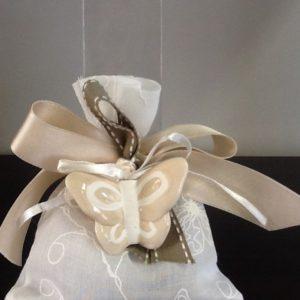 Bomboniera sacchetto ricamato di colore bianco confezionato 5 confetti e farfalla in ceramica beige,bianca e rosa conf.6 pezzi