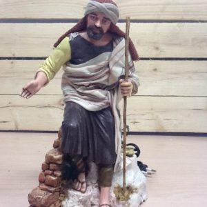 San Giuseppe seduto su muro in movimento,china il busto in avanti.in resina rifinito a mano con articolari in stoffa cm.28