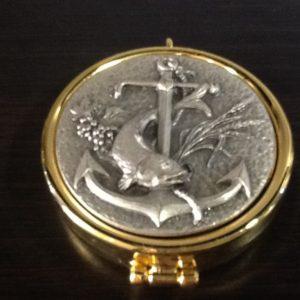 Teca in ottone dorato con placca in peltro decorata a rilievo con pesce/ancora diametro cm.5.5